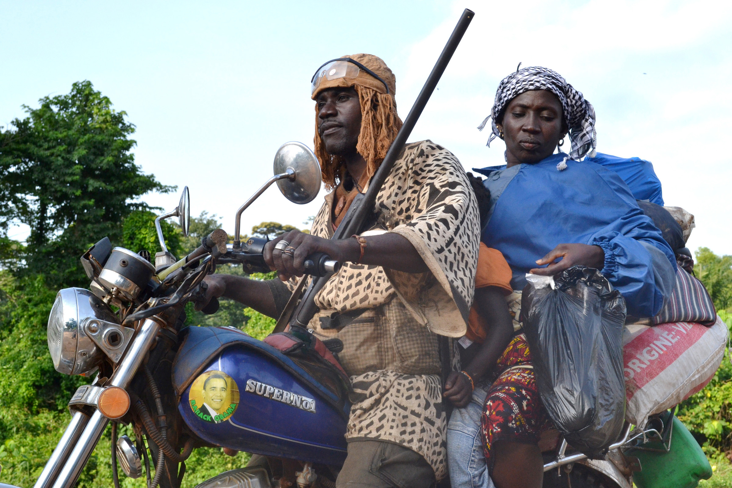 A woman and child mount a motorcycle driven by a dozo who is among those monitoring the road between Man and Duékoué in western Côte d'Ivoire. July 2011