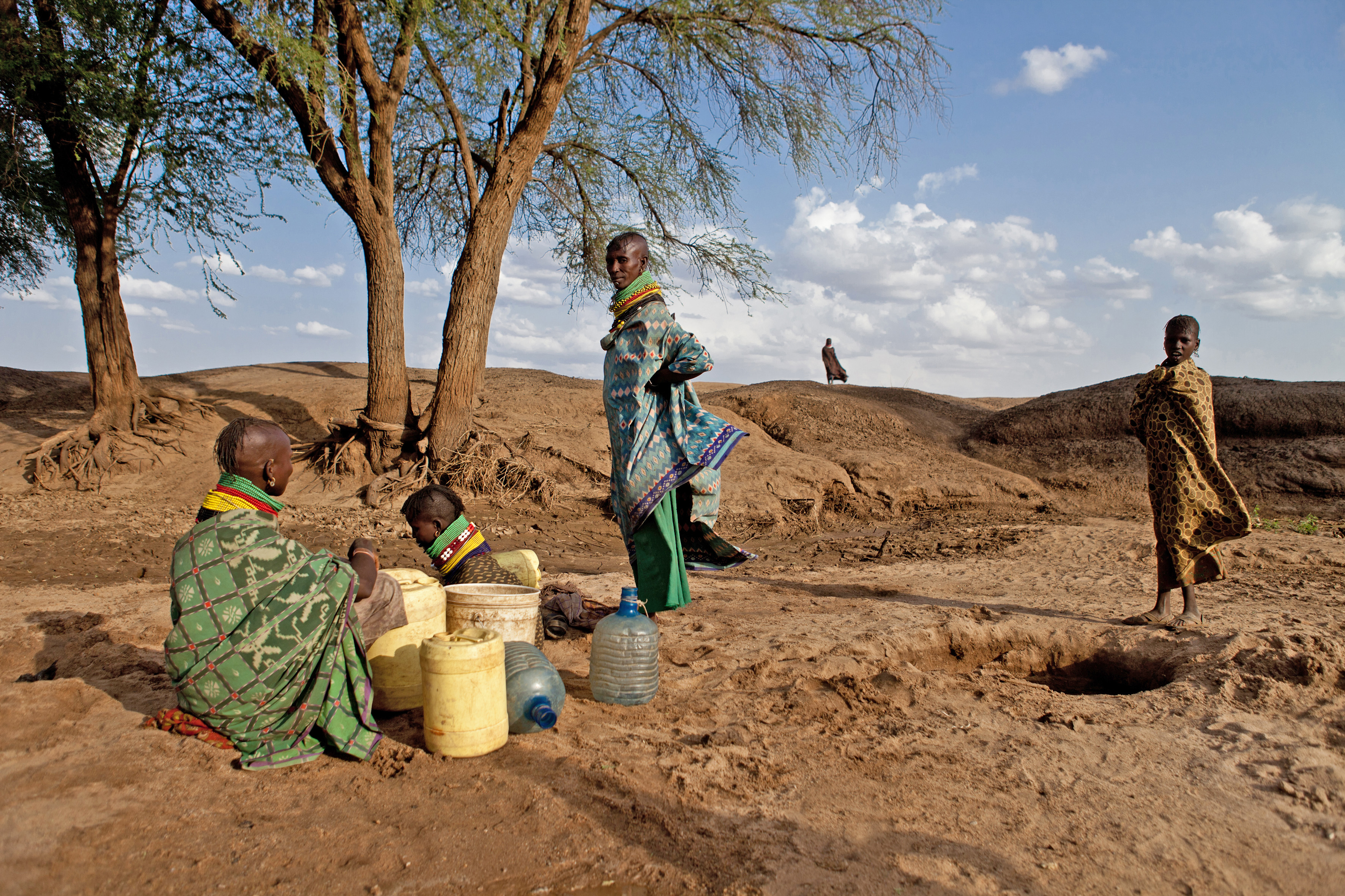 Turkana women dig for water on a dry river bed in northern Kenya