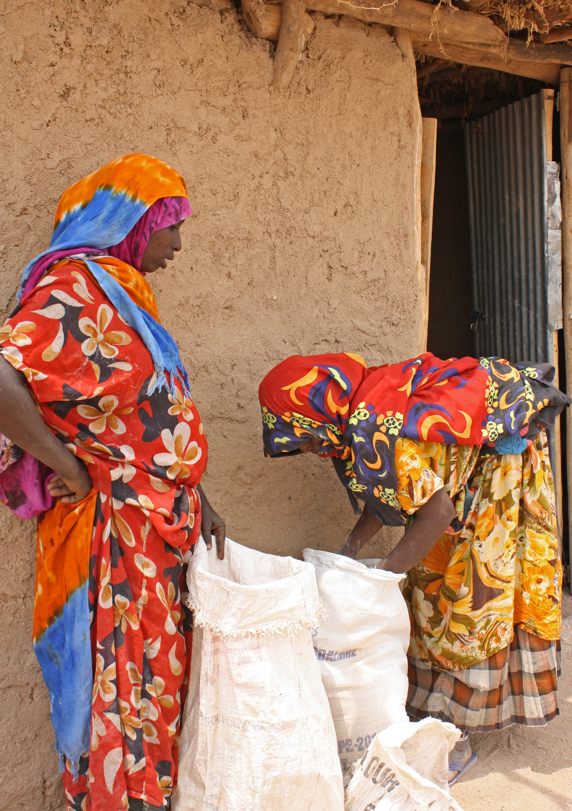 Women measuring out portions of corn soya blend for dispensing to mothers in Somali Region in Ethiopia