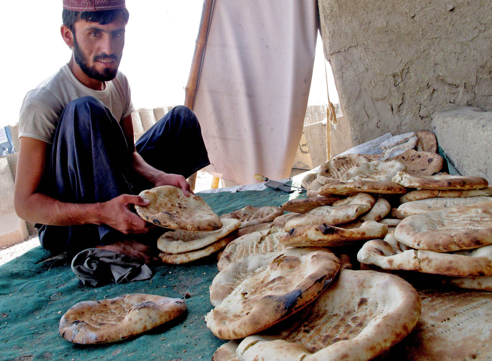 A baker sorts out freshly baked traditional Afghan naan bread in Arghandab Valley, southern Afghanistan