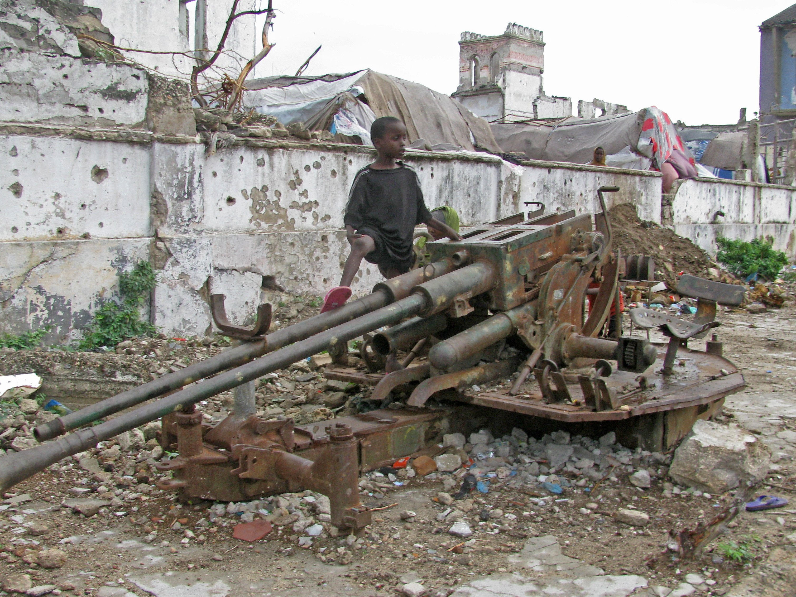 A child plays with an old artillery piece in Shangani District, Mogadishu