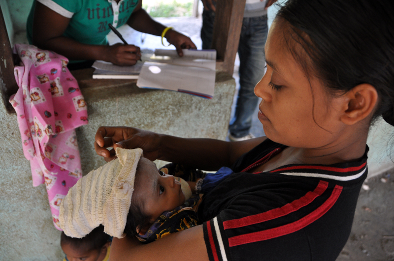 A mother holds her baby after it was weighed by health workers who traveled to the village of Asulao Sare, in Ermera District, to provide care to the isolated community