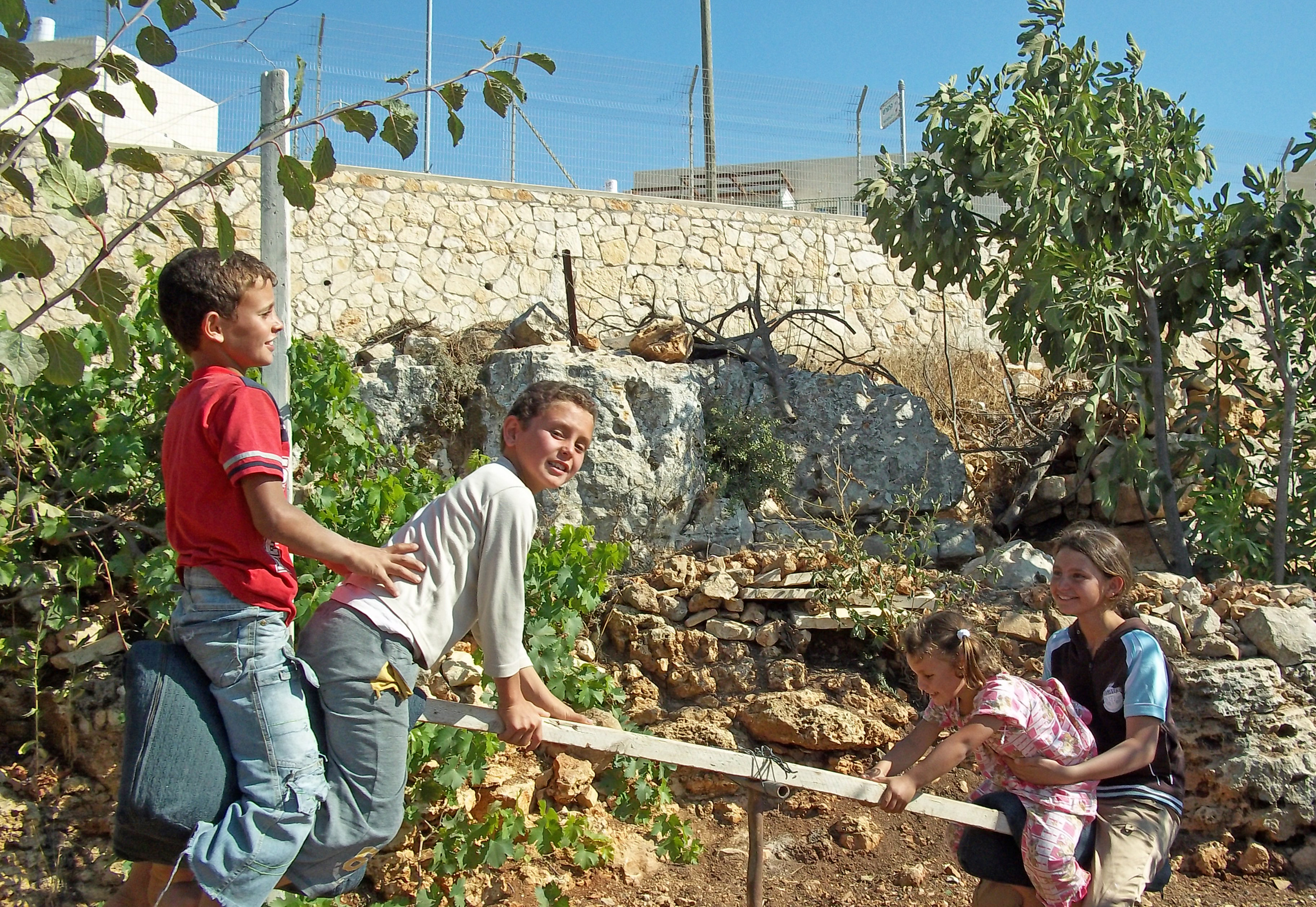 Children of the Saed family playing in Khallet Zakariya. Neighbouring Israeli settlement Alon Shvut can be seen in the background