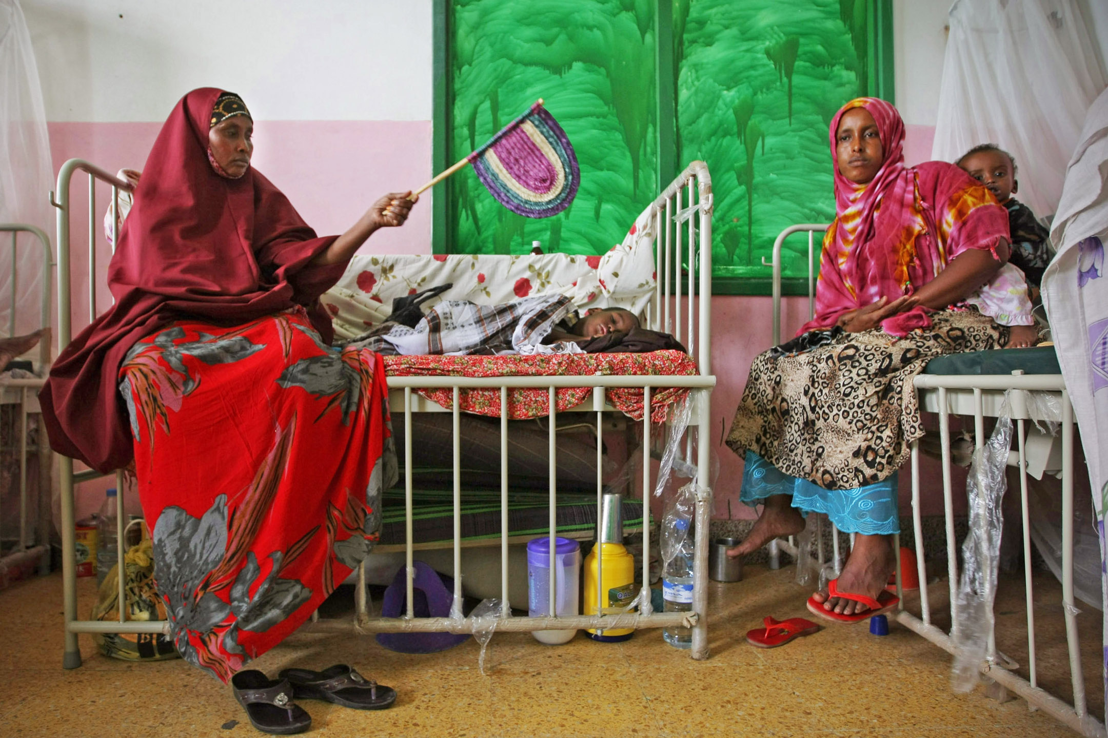 Mothers sit with their malnourished and dehydrated children in a ward at Banadir Hospital in the Somali capital Mogadishu