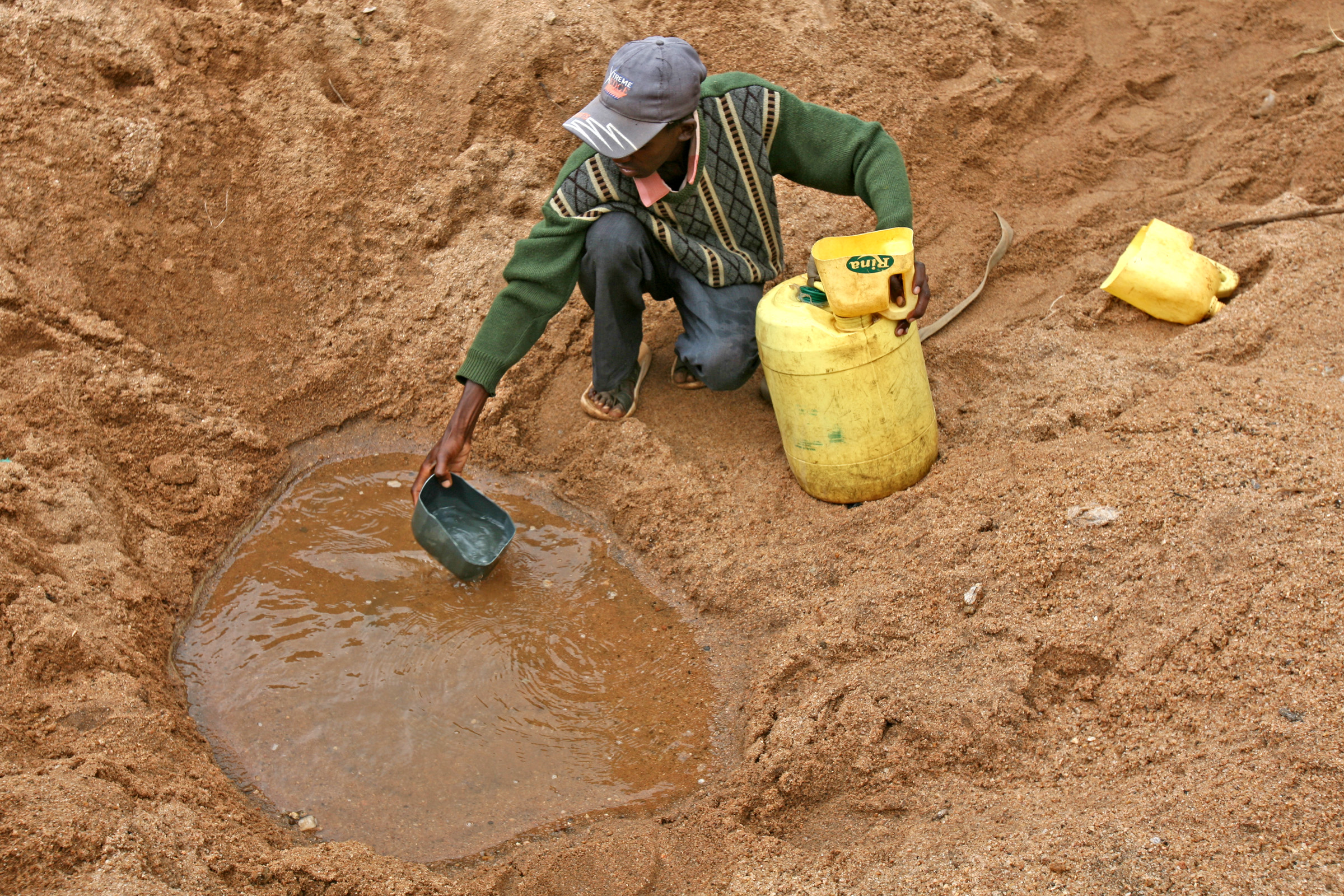 A man scoops water in a dry river bed in Mwingi, lower eastern Kenya