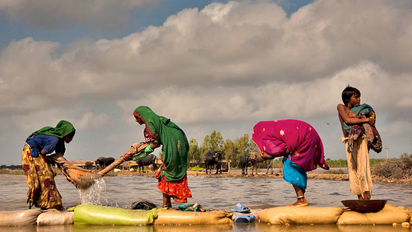 A flood-affected family wash their clothes in rising floodwaters next to their temporary camp in Digri, Sindh province