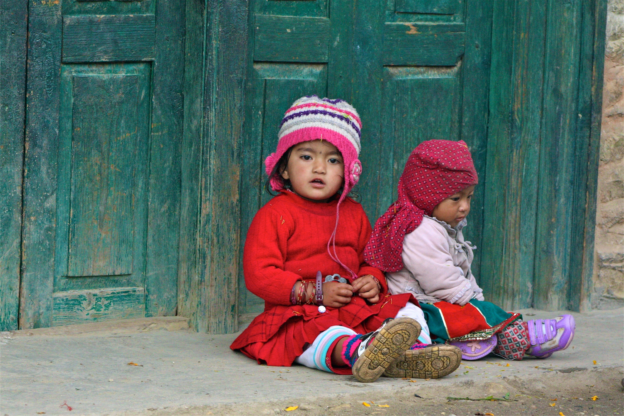 Girls sit near a doorway in Jumla, Nepal where girl babies are born to no fanfare, their birth and death at times never registered