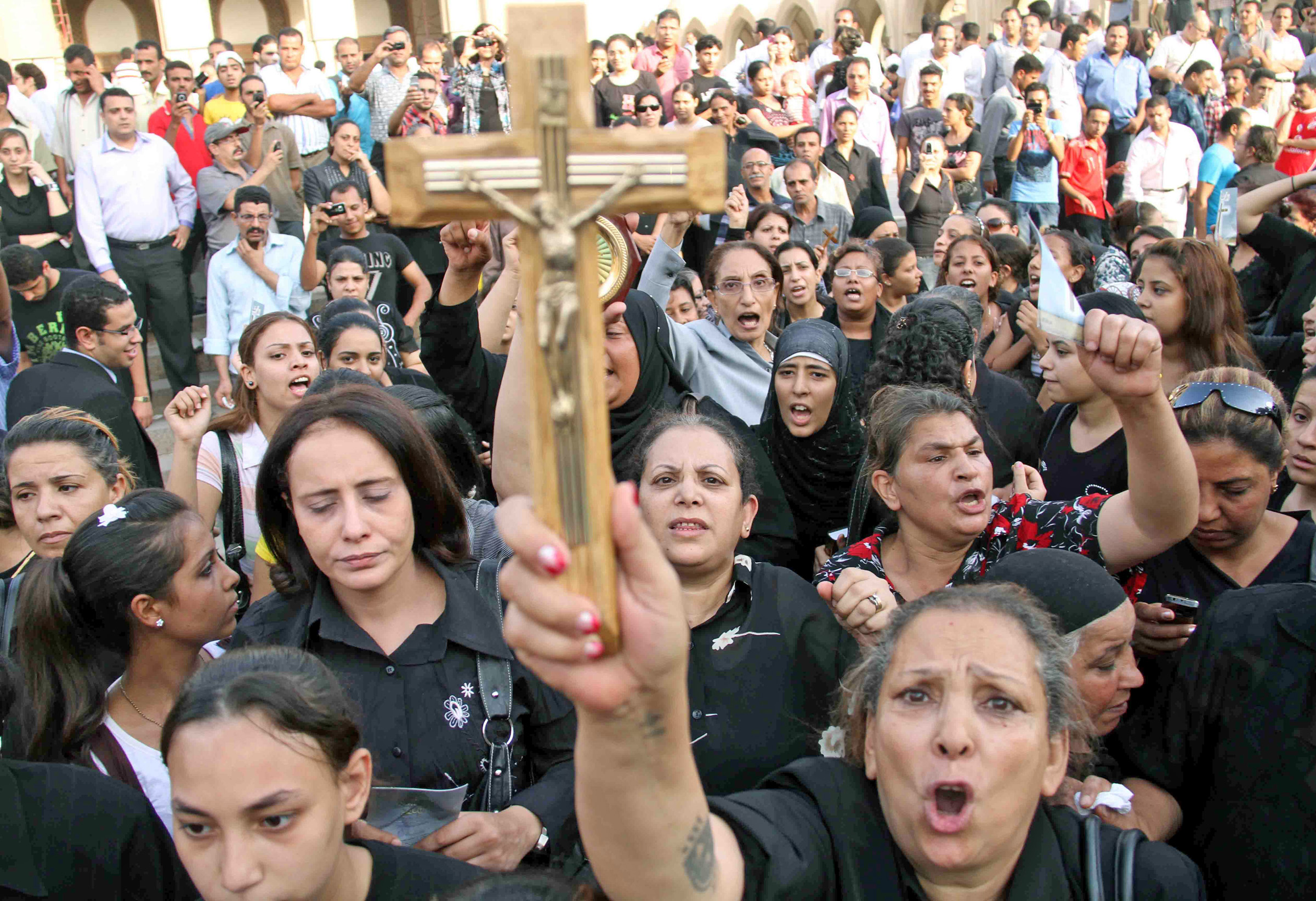 Raising the cross, Christian women protest against the killing of Christian demonstrators in a Sunday evening clash with military police in Cairo