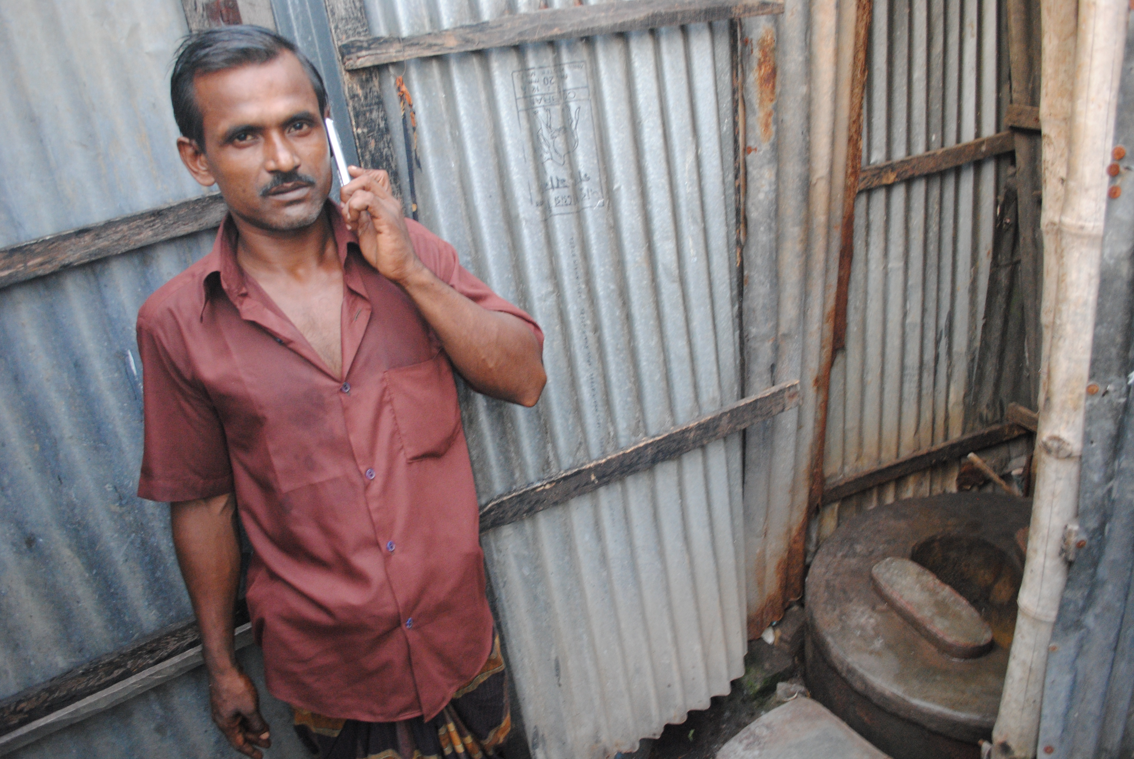 Abdul Malik, a 35-year-old rickshaw puller from Dhaka, shares a communal toilet with six families in the slums. Mobile phone usage has surged in recent years, while latrine usage has lagged