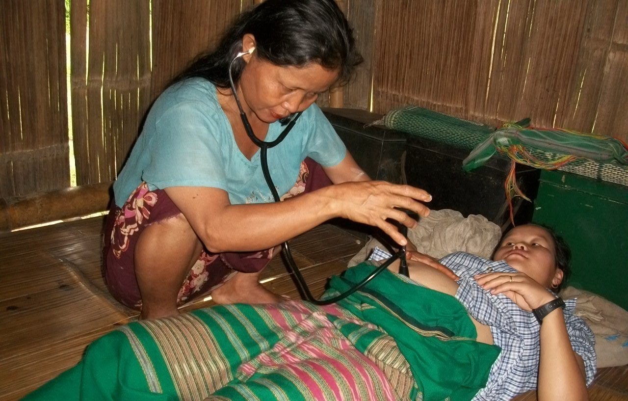 A traditional birth attendant examines a pregnant woman using a stethoscope in Karen state