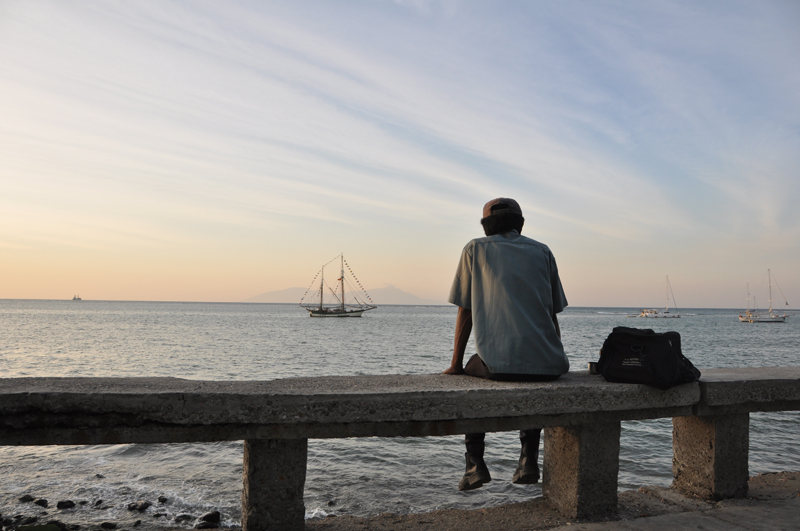 A man looks to the sea along the waterfront in Dili