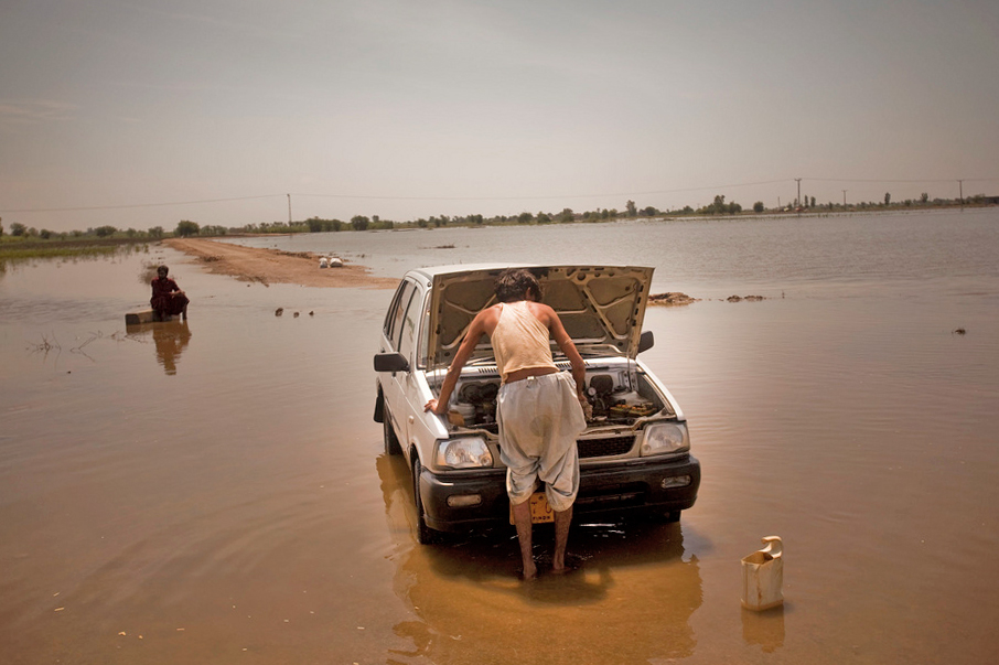A man tries to fix his car which broke down amidst the flood waters in Digri, Pakistan. Southern Pakistan