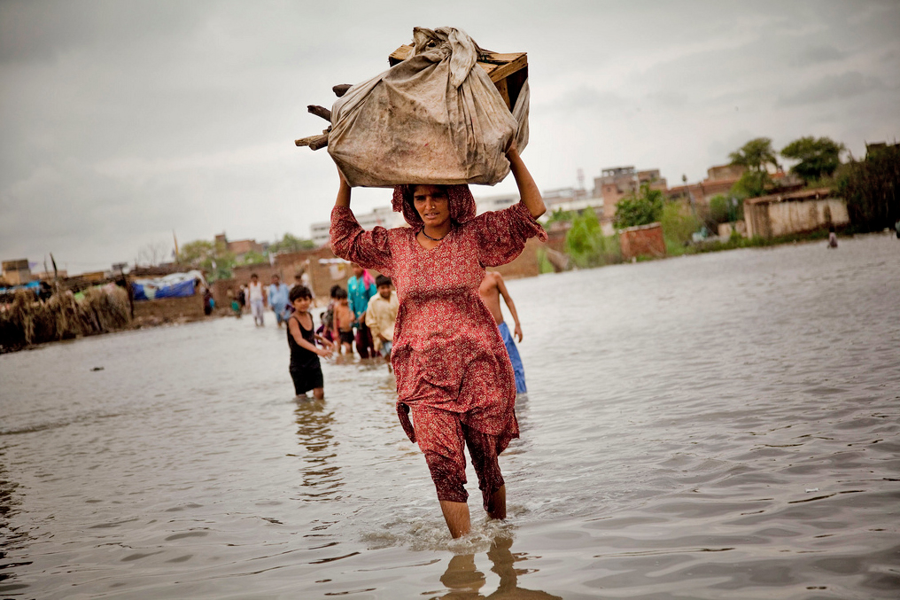 A woman carries her possessions through floodwaters in Hyderabad, Sindh province