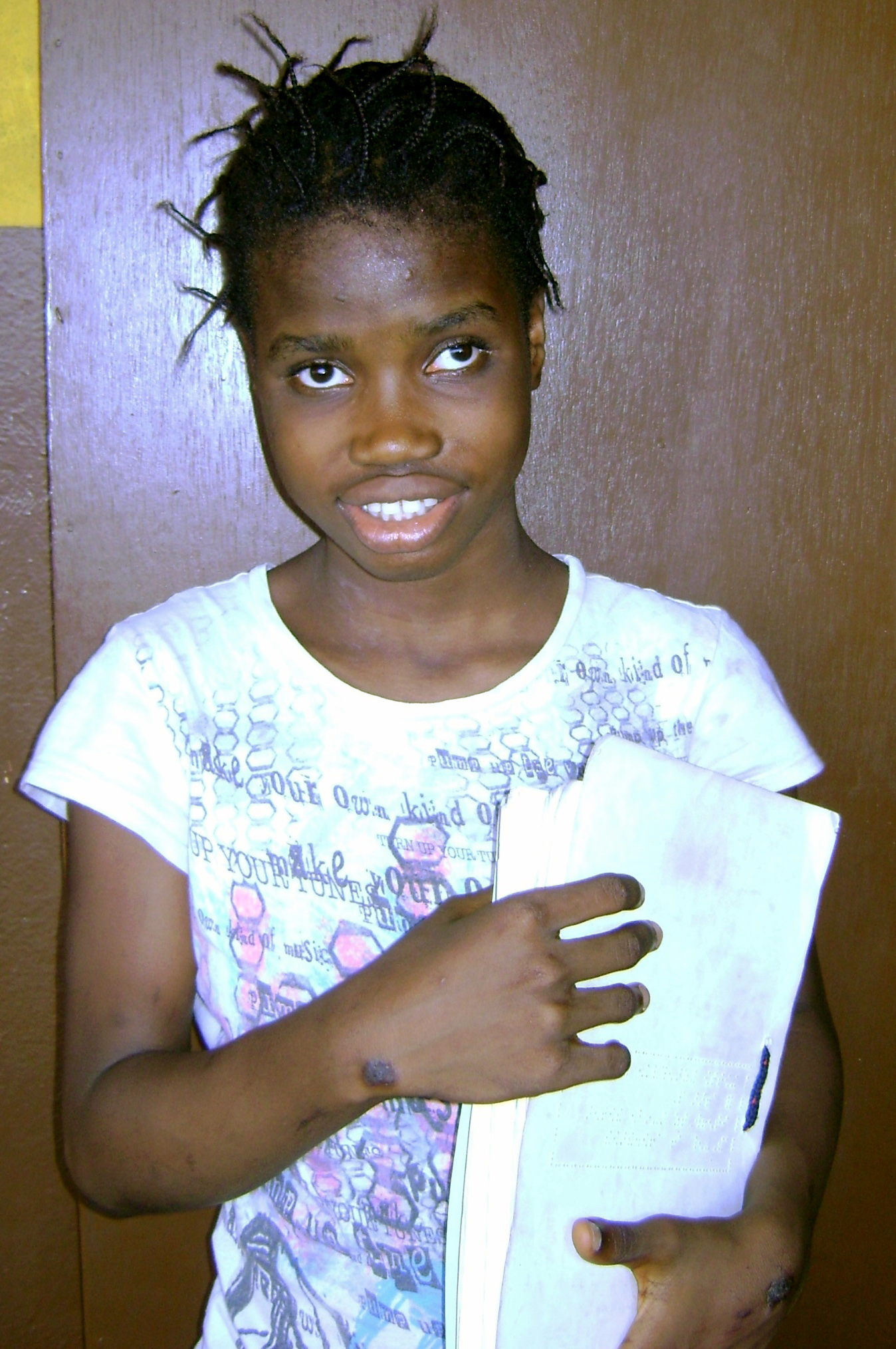 A blind student carrying her Braille notebook
