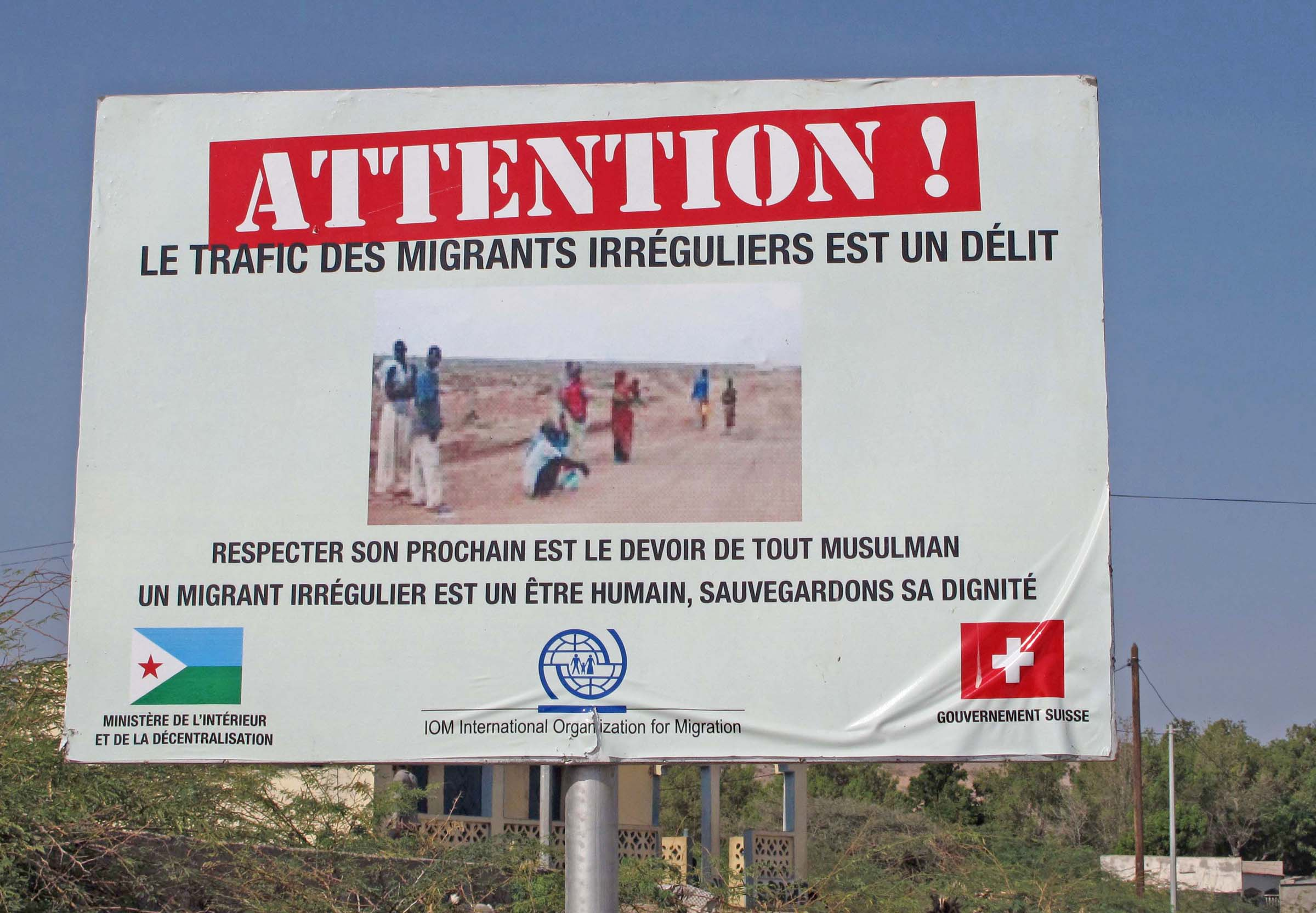 A sign on the road to Obock erected by the International Organization for Migration (IOM) reads: Attention! Trafficking migrants is an offense! Respecting your neighbour is the responsibility of every Muslim. Migrants are human beings – protect their di