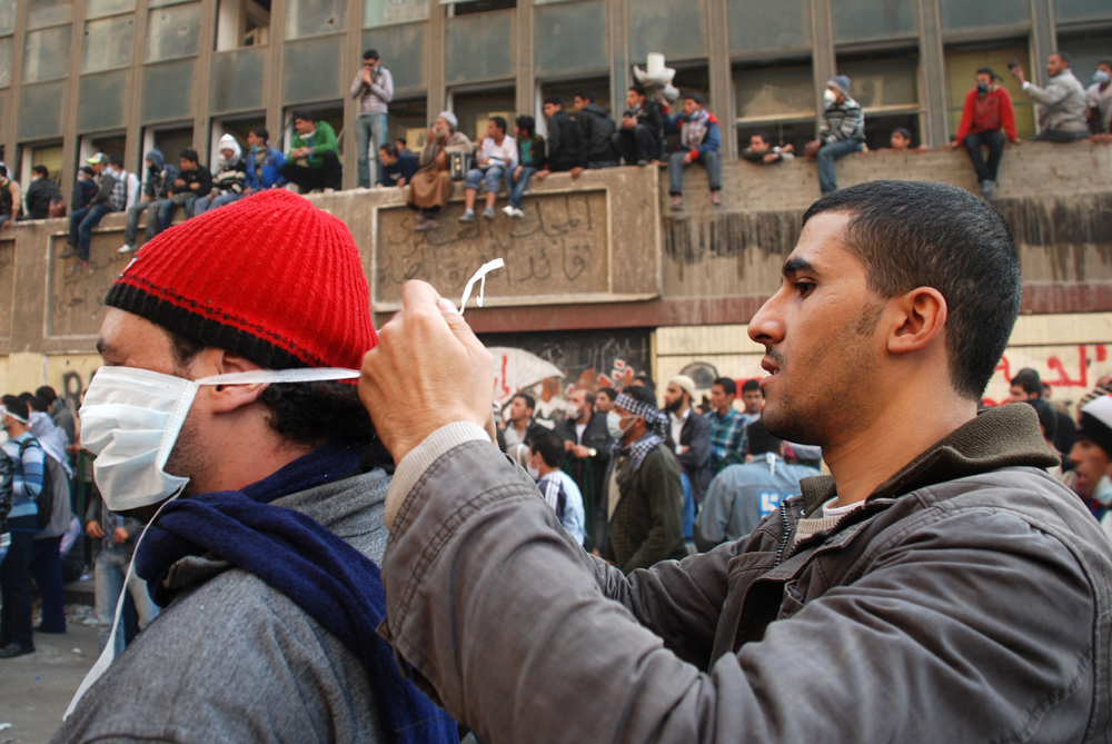 Two Egyptian men help each other fix papermasks used to protect against the tear gas-filled air in Cairo's Tahrir Square during protests against the ruling military council in November 2011