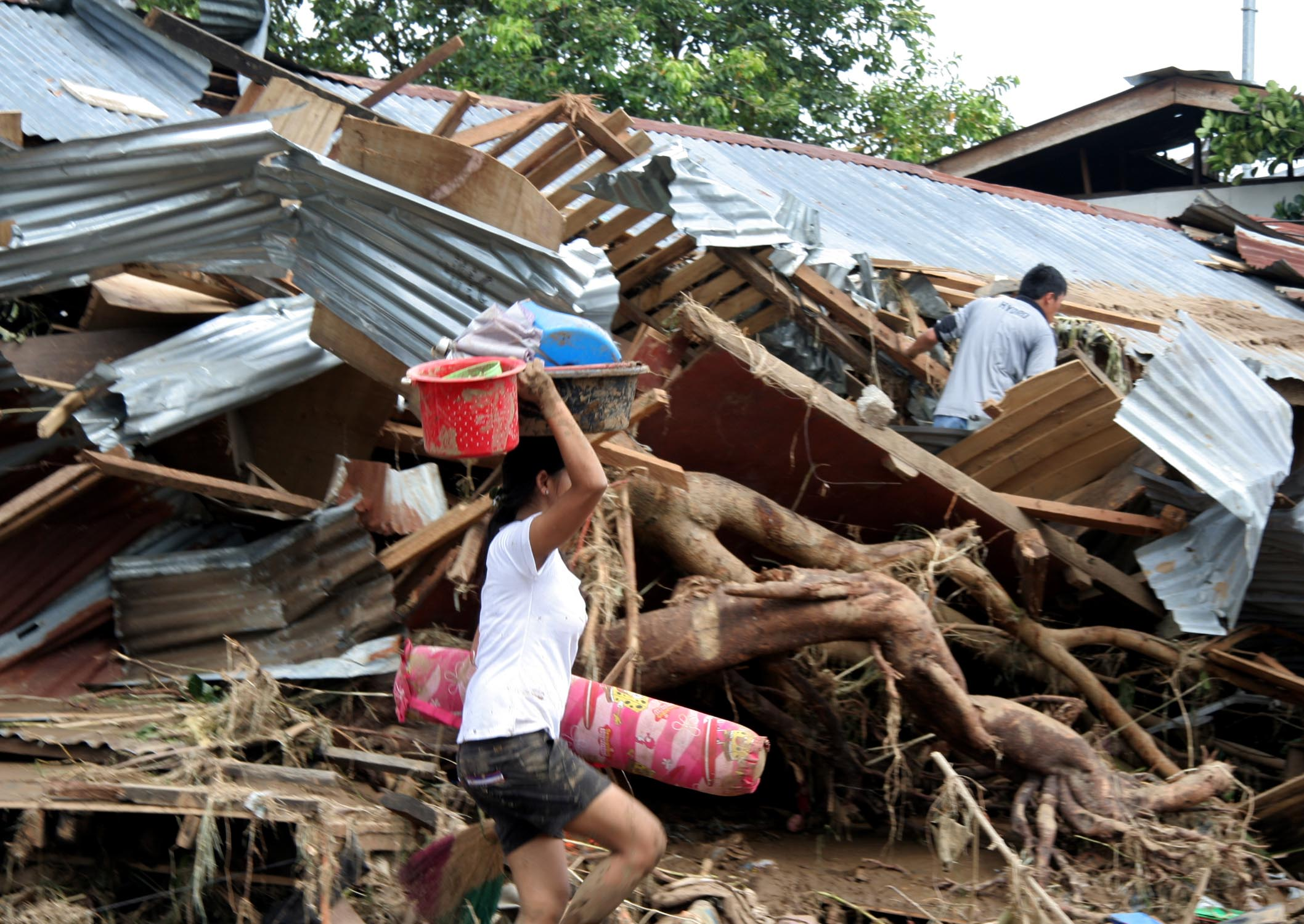 A woman salvages belongings from her ruined village in Mindanao. More than 600 people lost their lives when Tropical Storm Washi struck the island on 16 December 2011