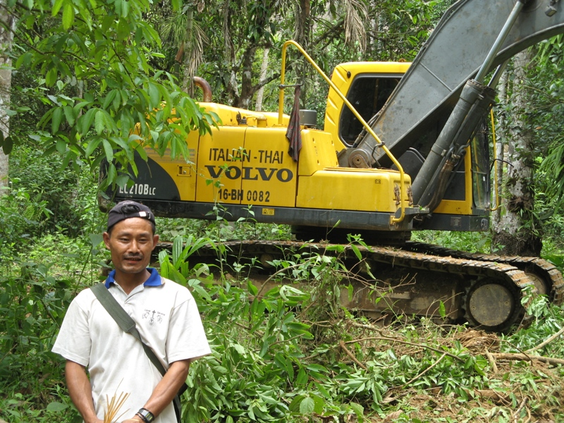 A local resident stands beside road construction equipment outside the southeastern city of Dawei. A major deep water port could displace thousands in the area
