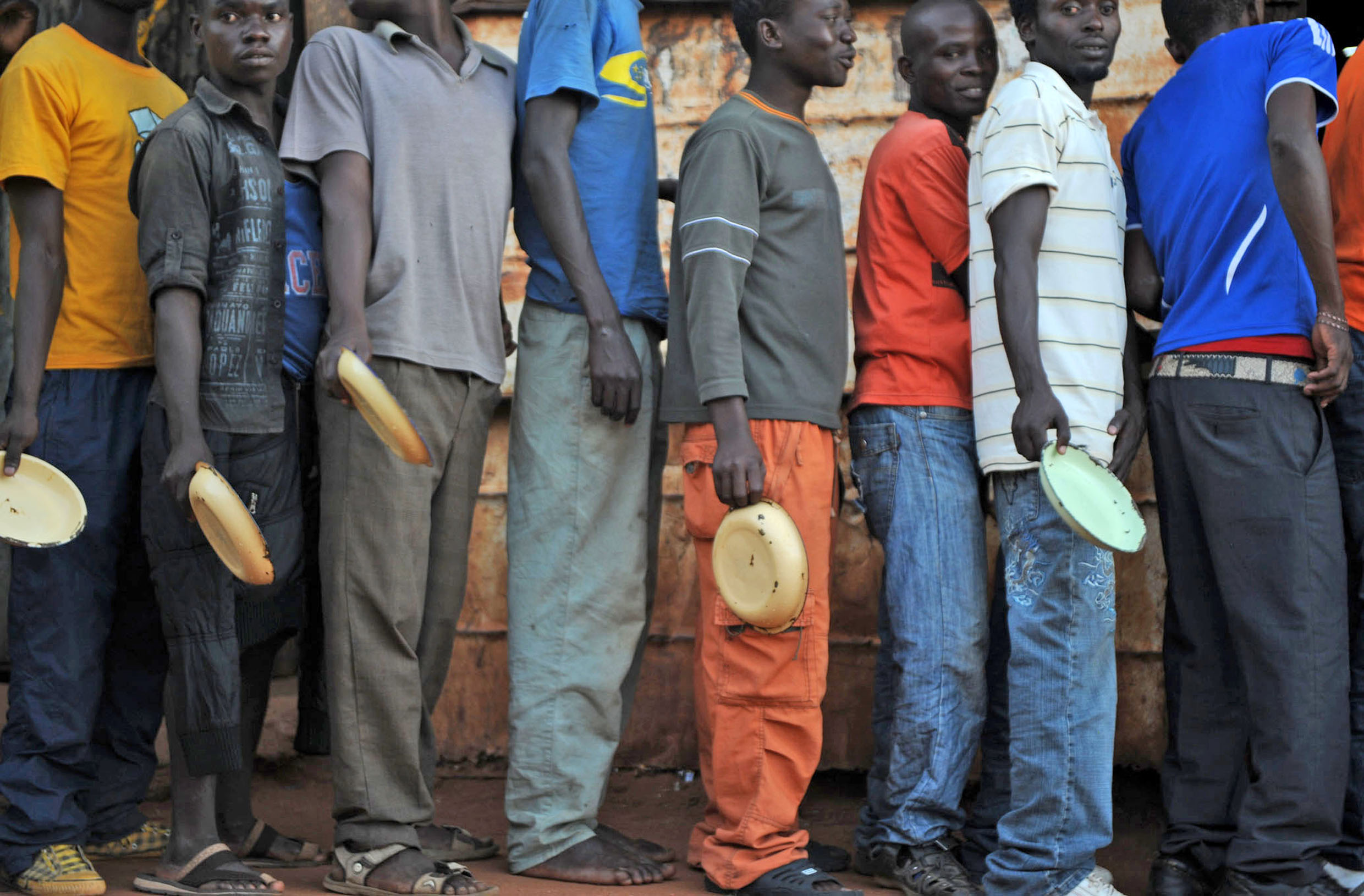 Migrants and asylum seekers at the 'I believe in Jesus Church' shelter for men in the South African border town of Musina queue up for a free hot meal, provided by the UN's Refugee Agency (UNHCR)