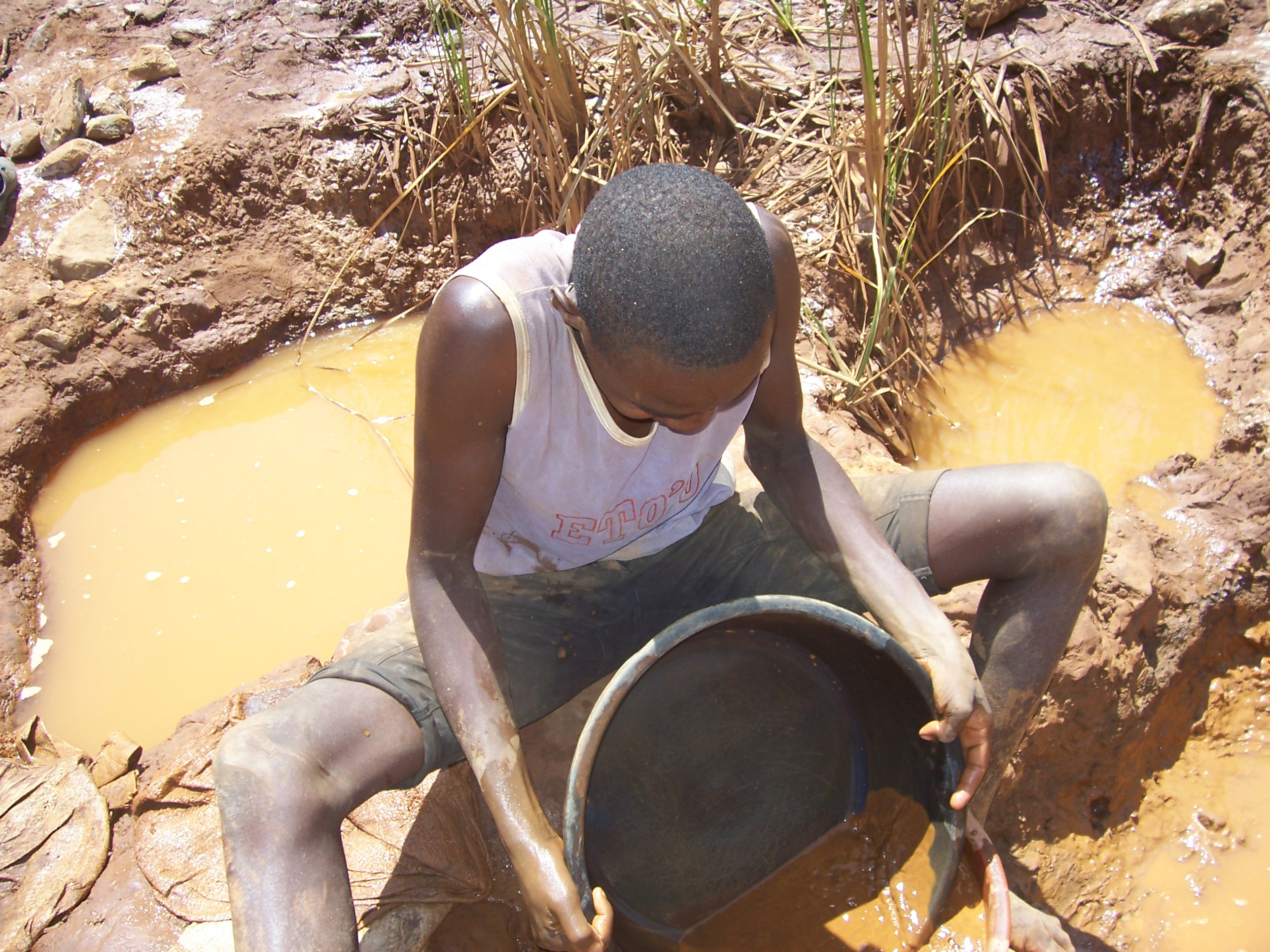A young man pans gold dust at a mine in western Kenya