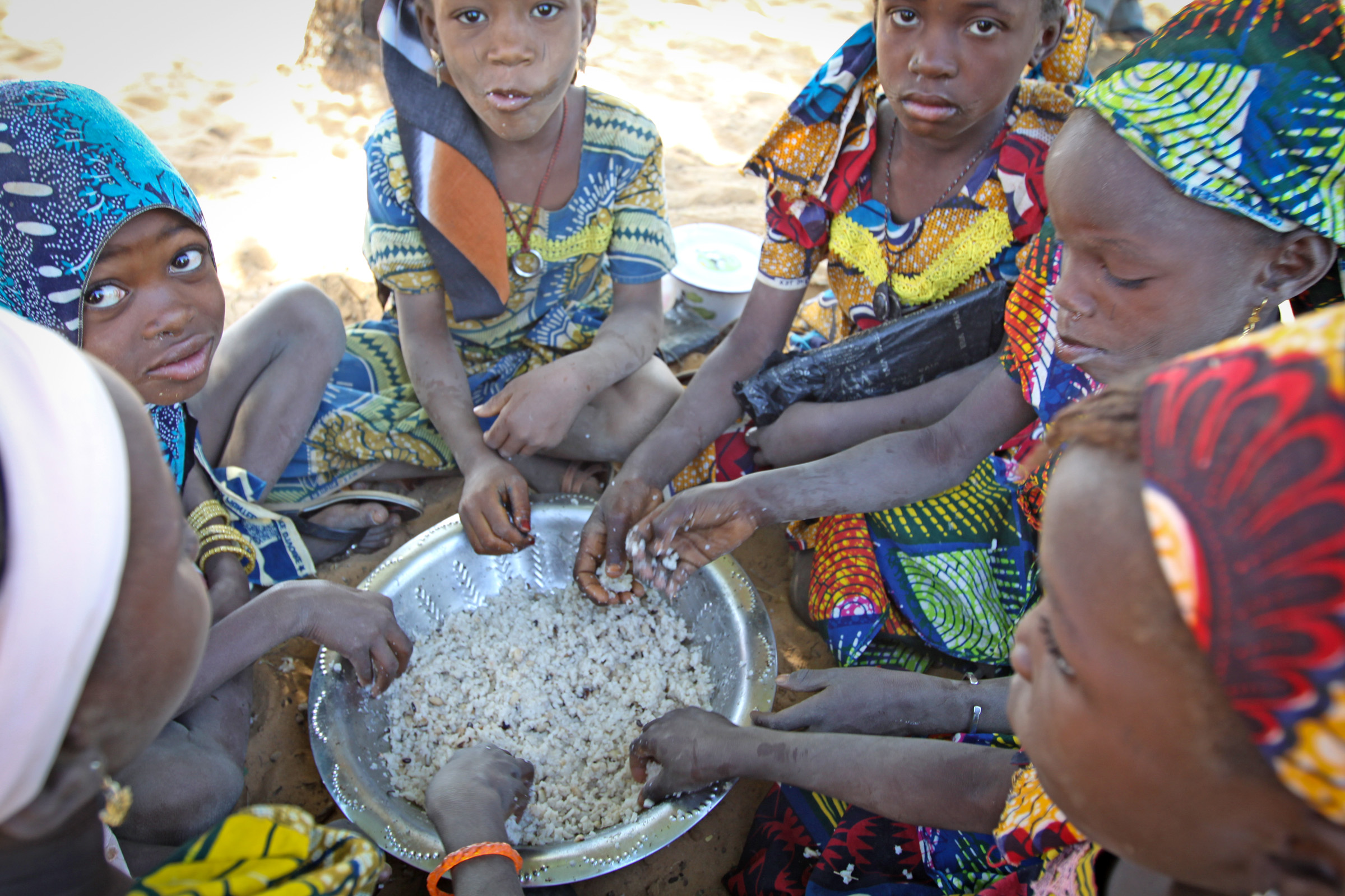 Young girls eating a midday meal at at World Food Programme school feeding centre near Bouza, Niger