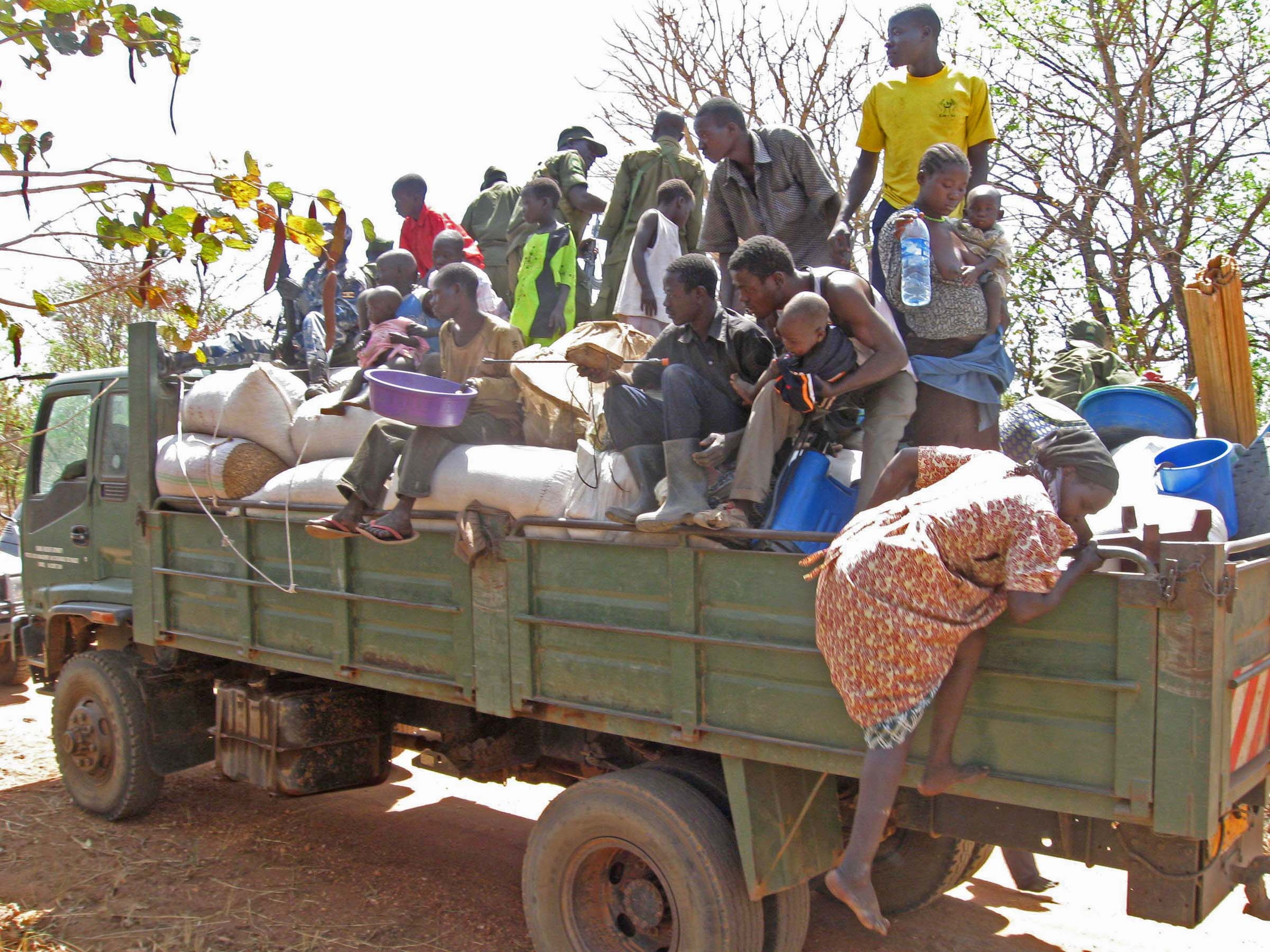 A woman climbs into a waiting truck in ongoing evictions in Apar, Amuru District