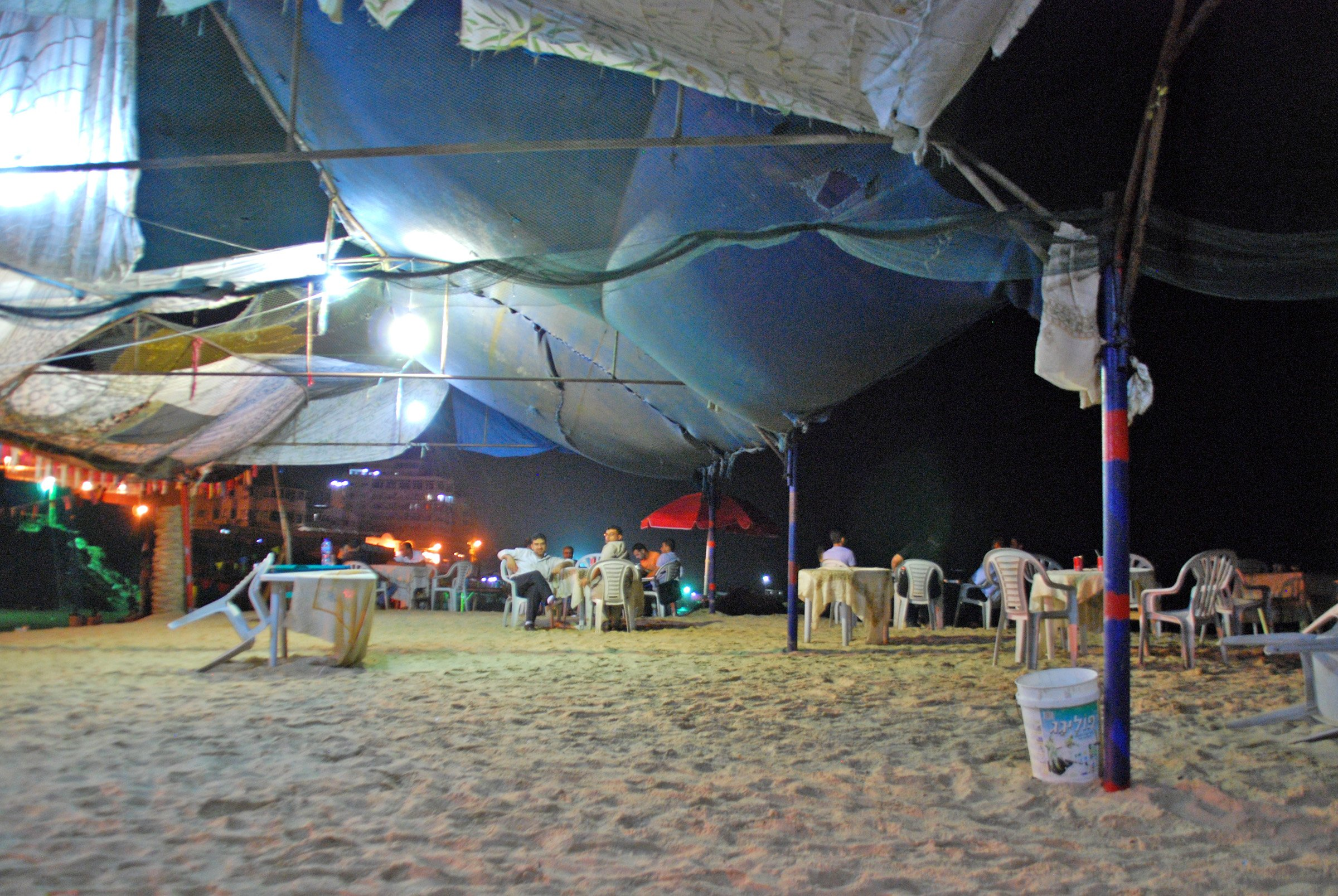 Women at a beachside restaurant close to Gaza City. The lights are powered by generators; daily electricity cuts are routine in the Gaza Strip