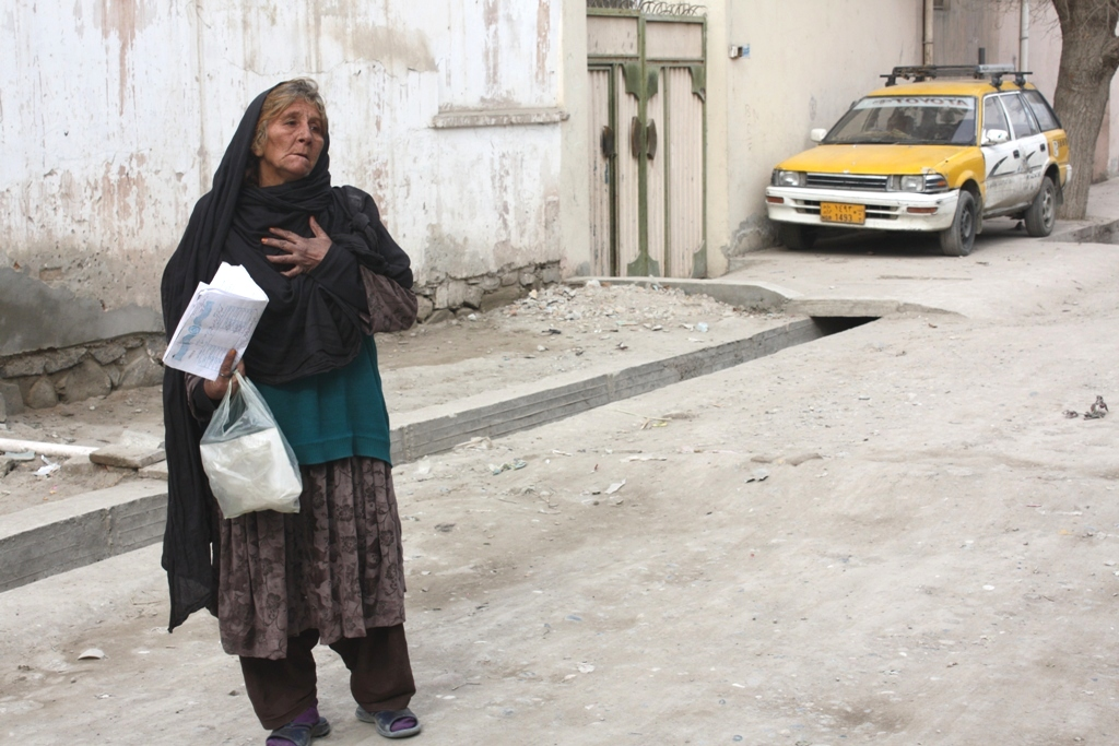 Baswra, an Afghan widow, begs for help outside an aid distribution point in Jalalabad, eastern Afghanistan. The mother of six returned from a refugee camp in Pakistan in 2002, but ten years later, still has no land or income