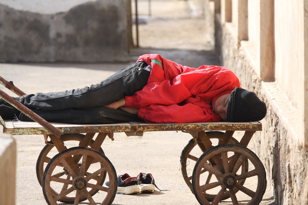 Jawad, 15, sleeps on a cart in a transit centre in Islam Qala, on the Afghan-Iranian border. He was separated from his guardian, his elder brother, and deported back to Afghanistan by Iranian officials