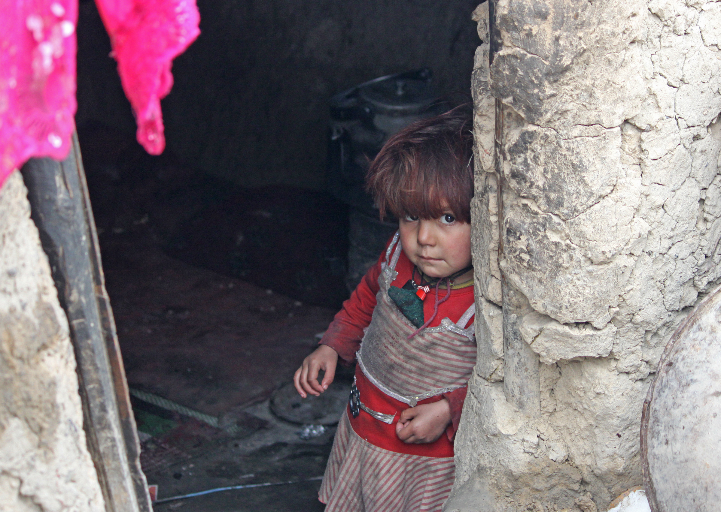 Besmillah's two-year old daughter, Nazia, looks out from their mud-hut, which doesn't have a door in the capital, Kabul
