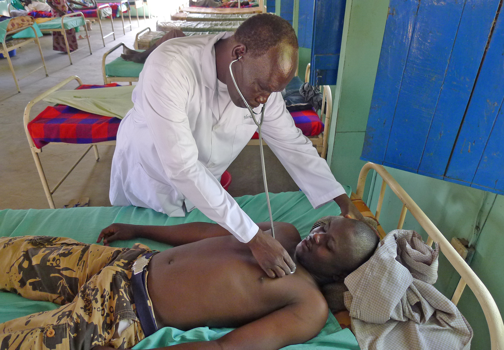 Elizeous Suror, Sleeping sickness program manager for MERLIN examines newly diagnosed patient Morgan Michael at Nimule hospital, Eastern Equatoria