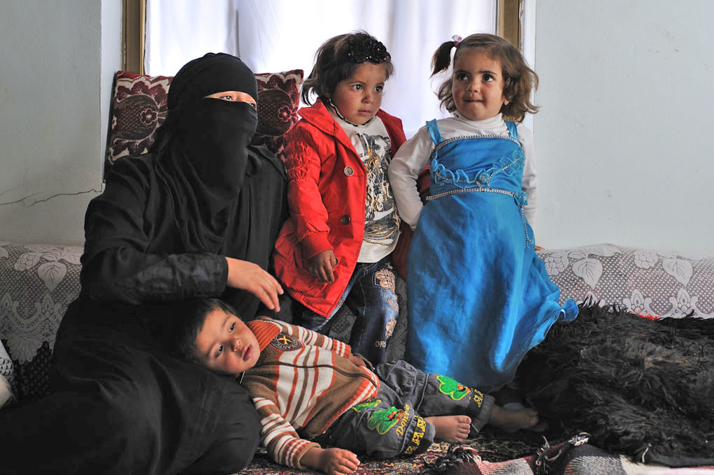 Aisha Haider sits with her daughters and son in a house they are living in temporarily due to damage to their own home. Members of the Murani family, their home was damaged by fighting between tribes from Arhab and the Republican Guard
