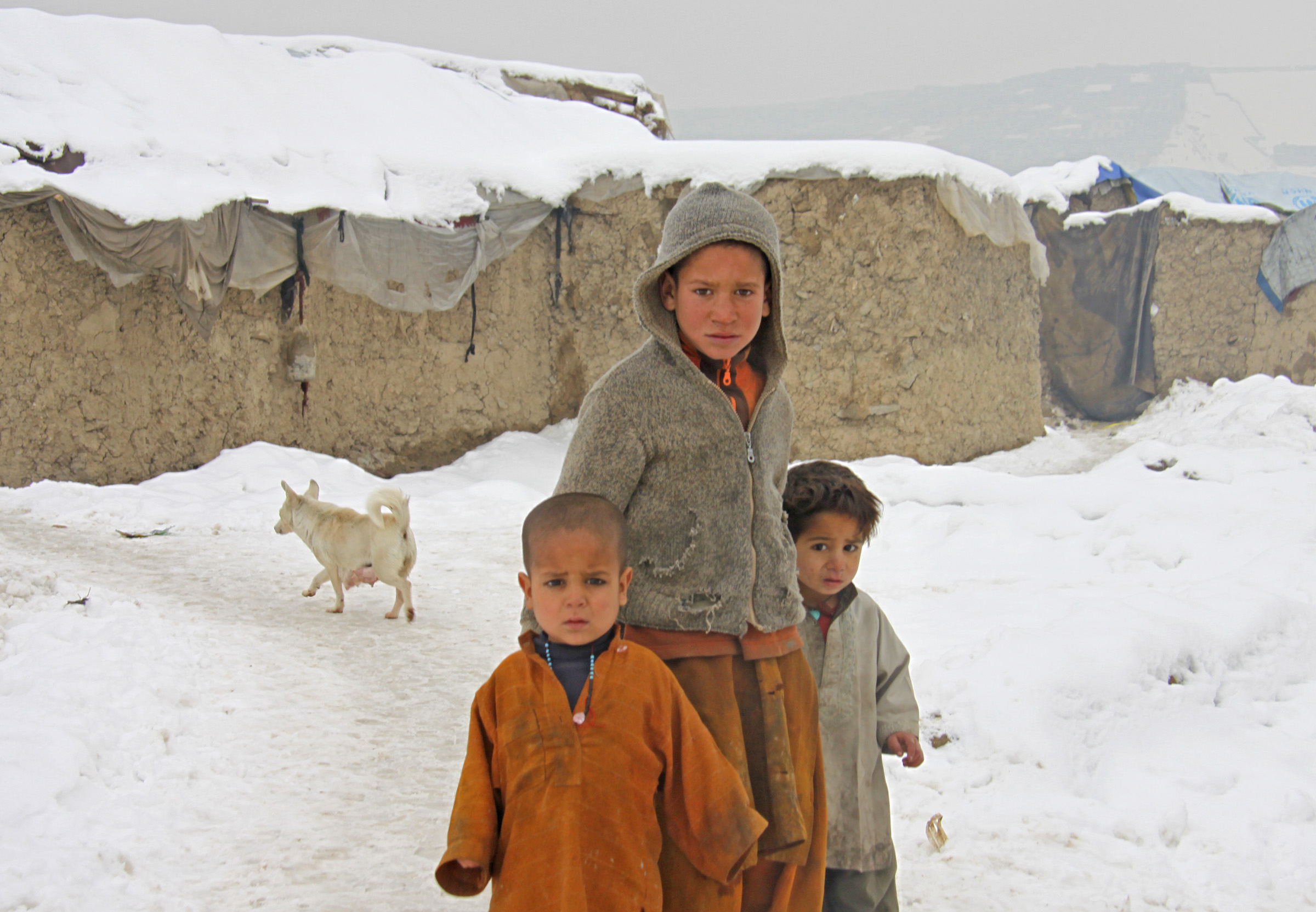 Children are exposed to cold weather in a makeshift settlement in Kabul