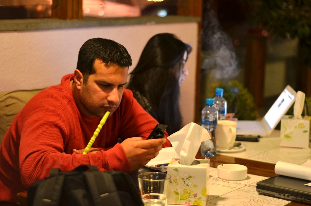 Ahmed Almasri, a Syrian refugee/activist in Jordan, sits in a trendy coffeeshop in Amman, where he organizes the illegal smuggling of medical and communications equipment into Syria
