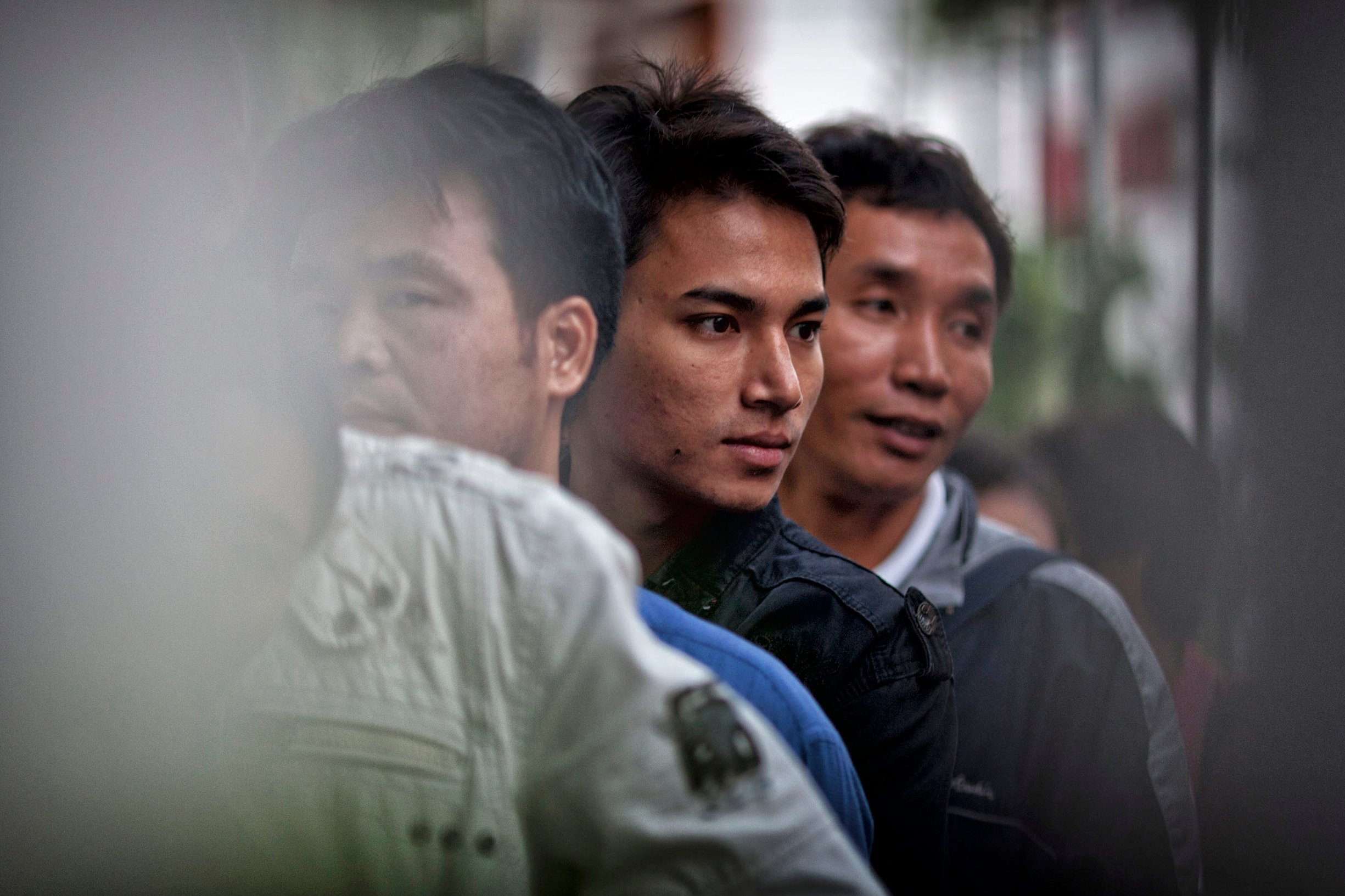 A group of young Burmese men wait to clear immigration at the Friendship Bridge at the Thailand-Border checkpoint in Mae Sot, Thailand. Thousands of men each year migrate to Thailand in search of work