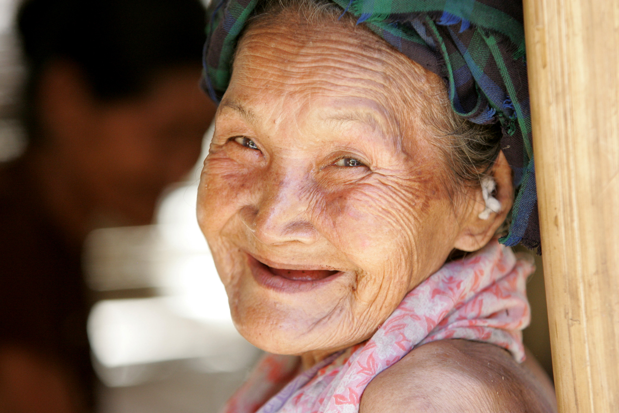An ethnic Karen refugee smiles as others make new homes in the village of El Htu Hat, Myanmar, along the Thai-Burmese border