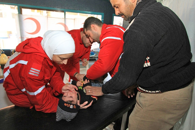 Syrian Arab Red Crescent volunteers comfort an injured child while a SARC doctor carries out an examination in Bludan, Syria