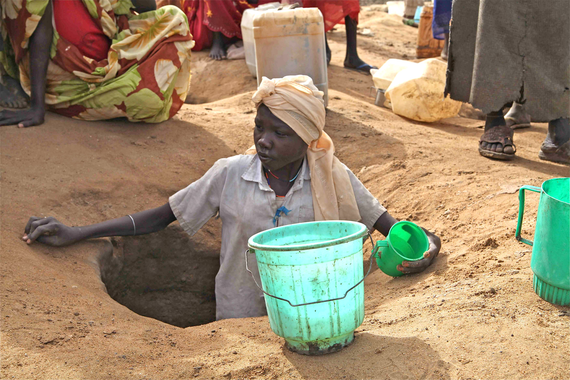 Girl digs for water in Jamam refugee camp, South Sudan