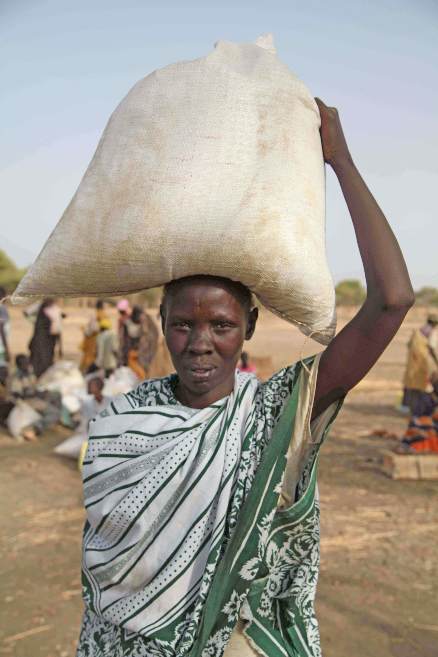A lady carries home precious food stocks that will feed her family while they plant crops