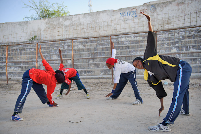 Female runners with the Somali Athletics Federation stretch at Mogadishu's shelled-out Konis stadium on March 10, 2012. In a society where the vast majority of women wear the full Islamic veil, girls doing sport like this is a significant break from the n