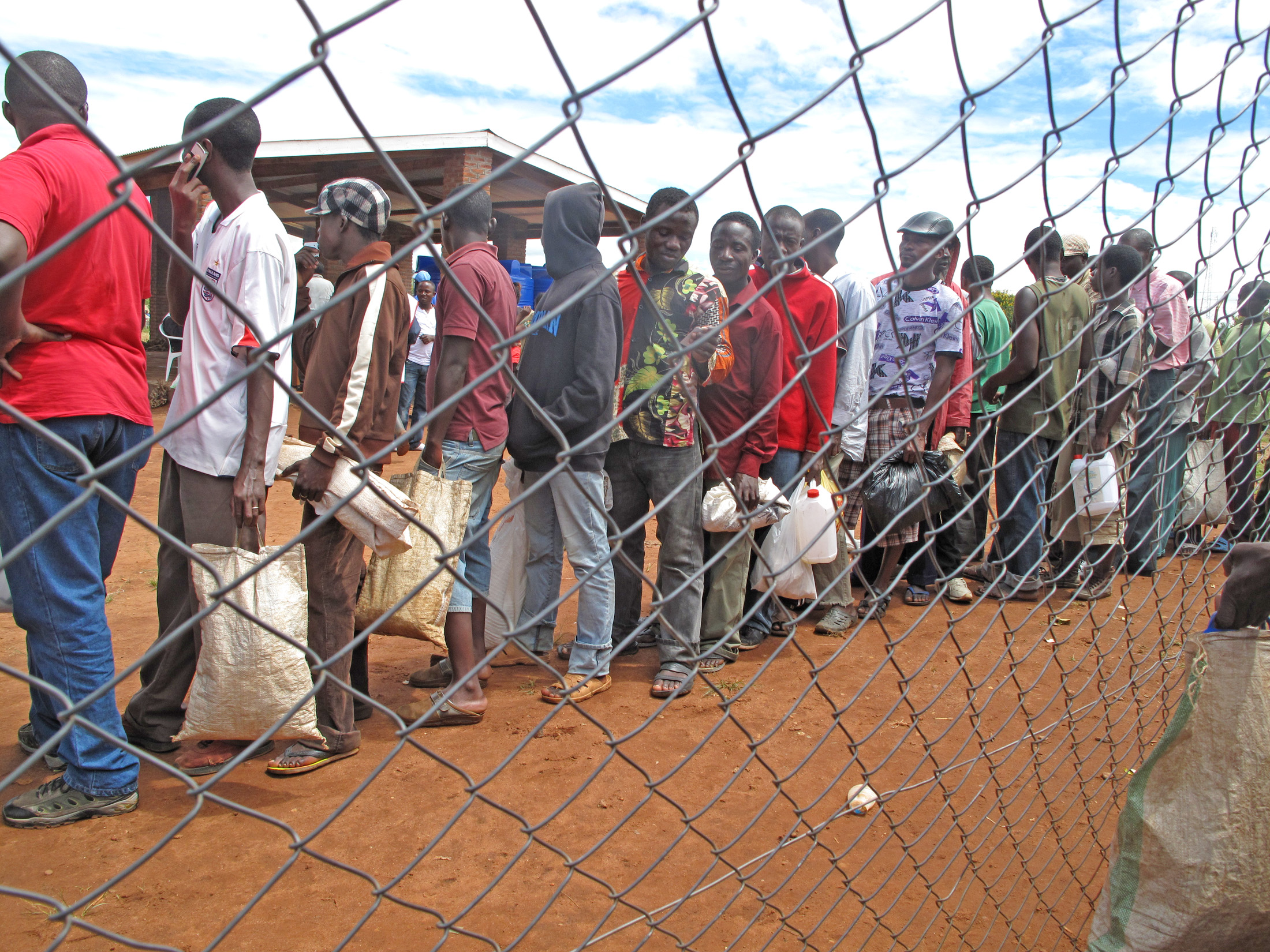 Refugees at Dzaleka camp in Malawi wait in line to collect their monthly food rations which were cut by half in March 2012 due to a funding shortfall