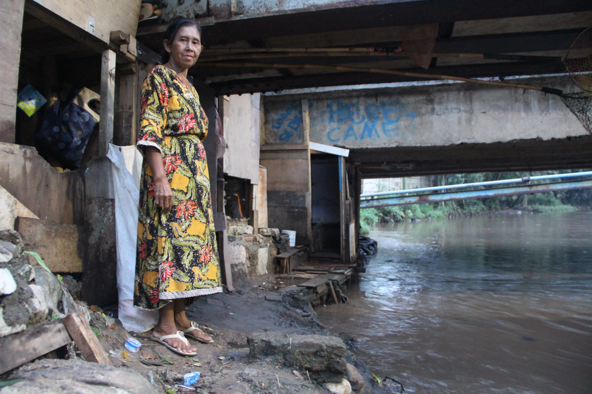 Ibu Sutria along West Java's Krukut River in Indonesia, along which millions live and depend on the polluted river