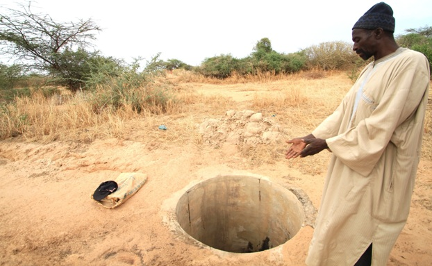 An inhabitant of Mbar Toubab village in Syar district in northern Senegal shows IRIN an empty well following poor rains in 2011