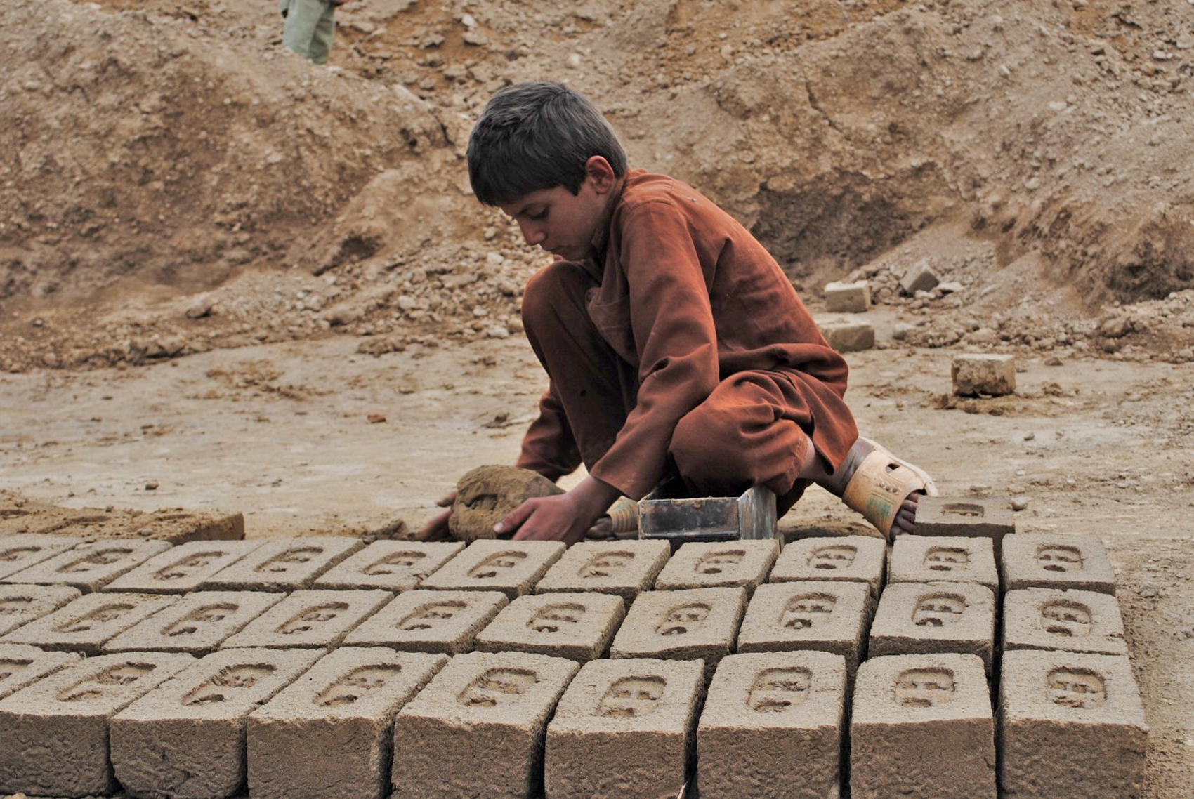 A boy makes bricks at a kiln in Afghanistan