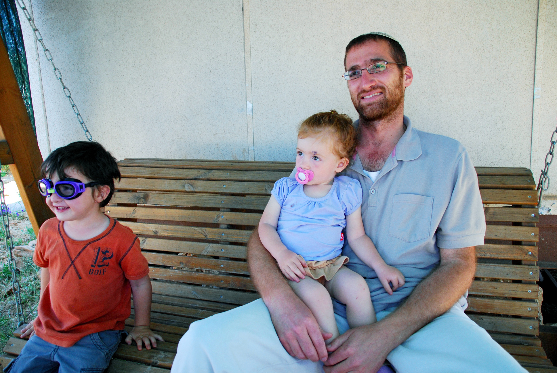 Itai Hemo with his children in front of his caravan in the illegal outpost of Migron, slated for evacuation on August 1