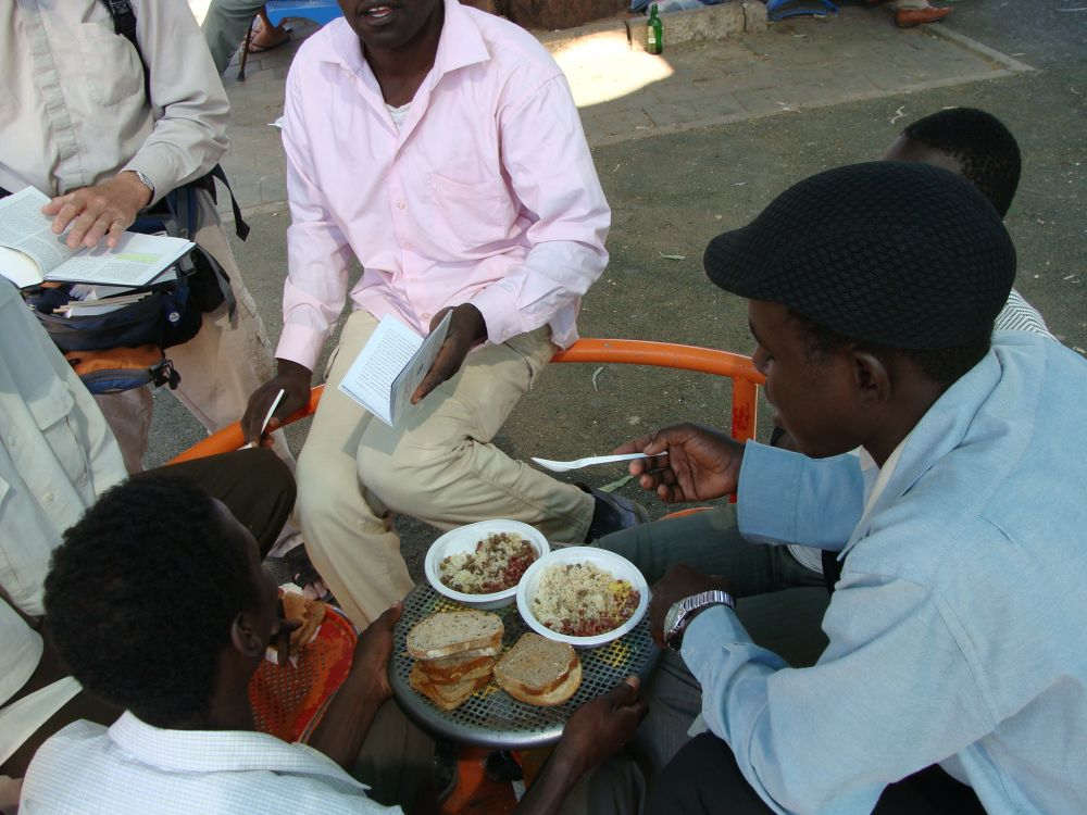 African migrants eating in a park in Tel Aviv