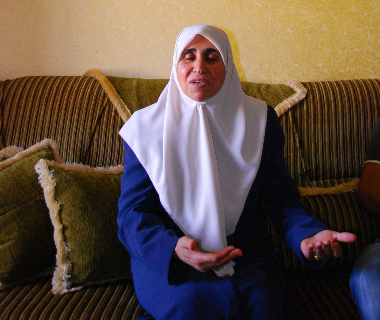 Nazmeh Mustafa in her home in Jenin. In the background a photograph of her husband (right) Wasfe Kabaha, a former Hamas minister for prisoner affairs