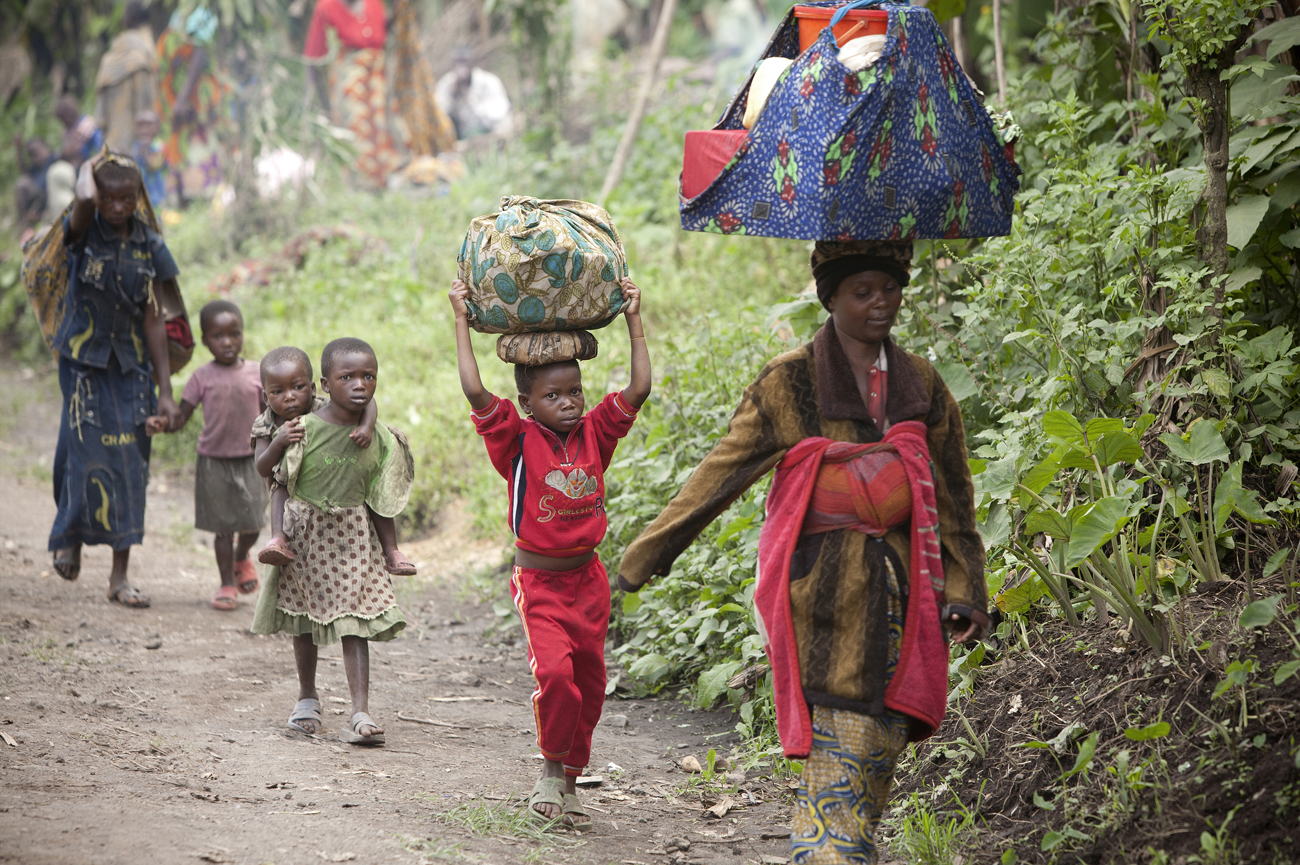 Congolese civilians carry their belongings as they escape the recent fighting between Congolese government forces and rebels close to Rutshuru in North Kivu in the east of the Democratic Republic of Congo on 20 May 2012