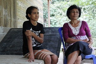 Maria De Fatima Kalcona, formerly a member of the Timorese resistance during Indonesia's 1975-1999 occupation, sits with her daughter outside their home in Dili