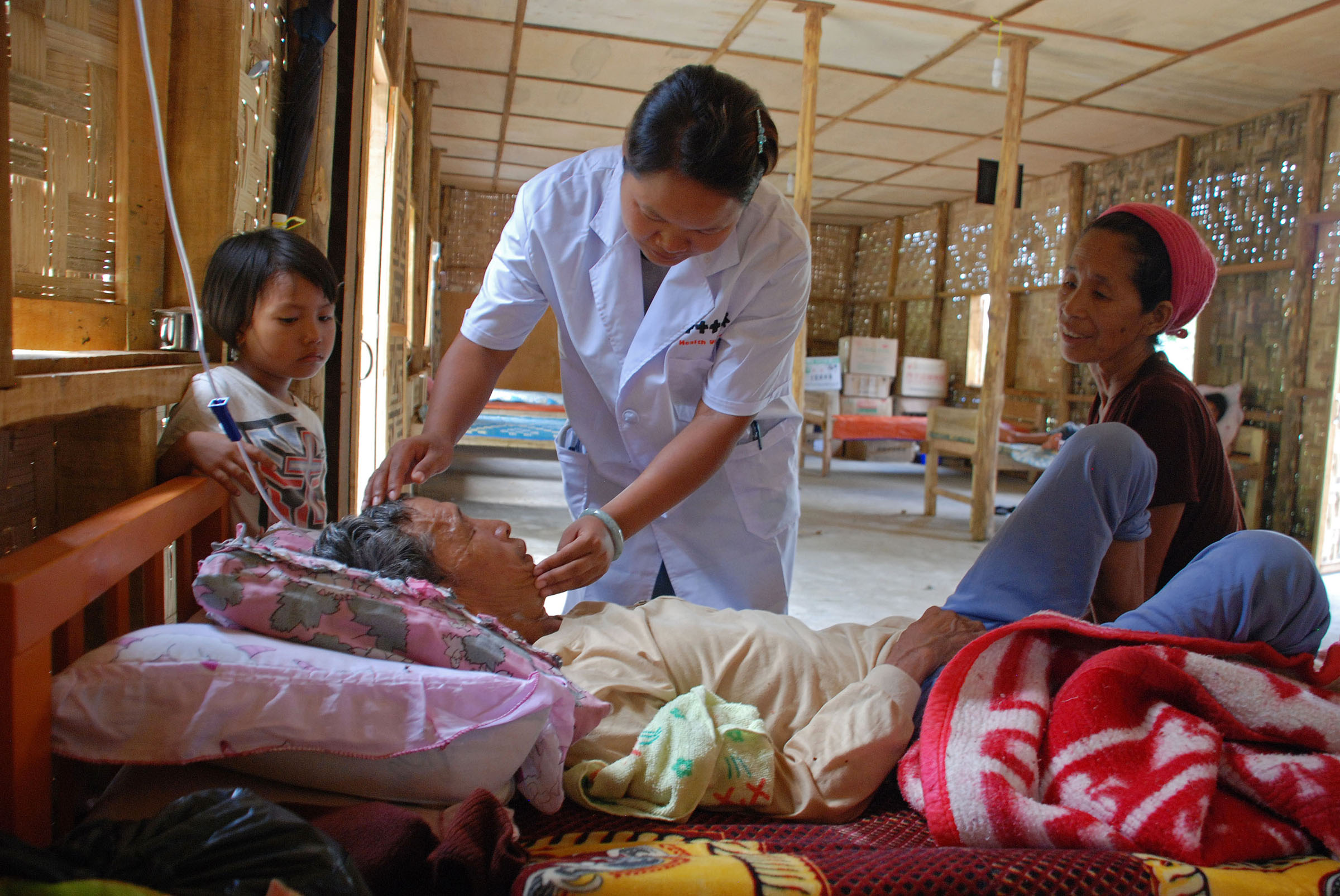 Sau Myaw head medical doctor at the Je Yang IDP camp treats an elderly patient
